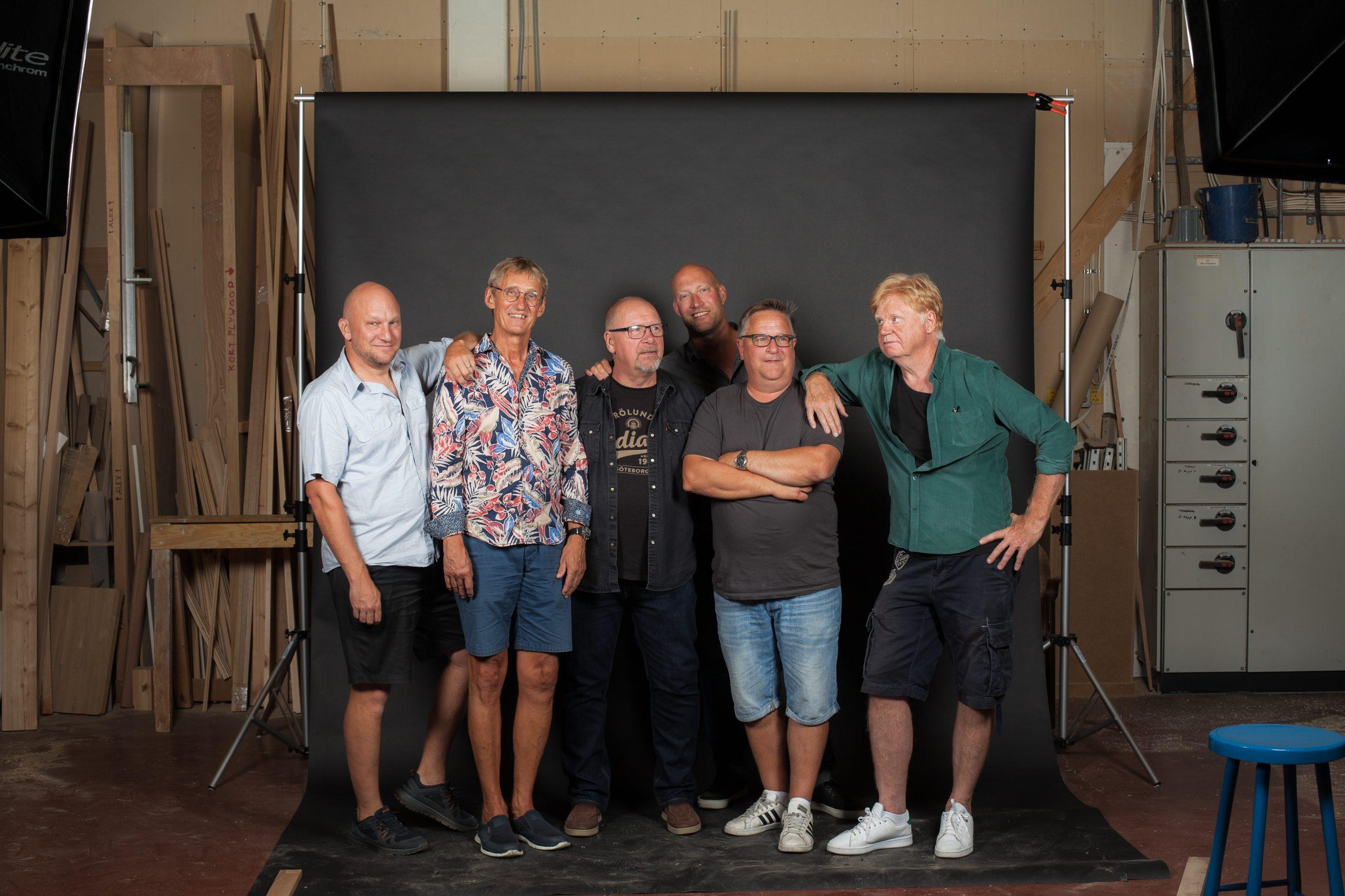 Bild på bandmedlemmarna i ett snickeri
